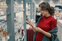 Customer choosing crystal glasses utensil dishes in the supermarket mall. Female customer choosing crystal glasses utensil dishes in the supermarket mall. She is Royalty Free Stock Image
