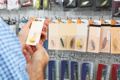 Customer choosing fishing equipment in sports shop, closeup. Space for text royalty free stock photography