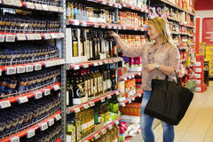 Customer Choosing Olive Oil In Supermarket Stock Photos