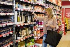 Customer Choosing Olive Oil In Supermarket. Smiling mature female customer choosing olive oil in supermarket royalty free stock photo