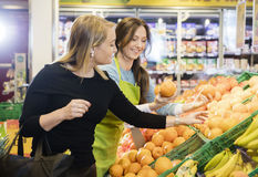 Customer Choosing Oranges By Saleswoman In Store. Happy female customer choosing oranges by saleswoman in grocery store royalty free stock image