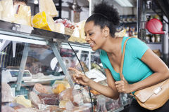 Customer Choosing Product From Display Cabinet Royalty Free Stock Photography
