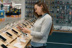 Customer choosing smartphone in the mobile phone shop. Smart female customer choosing smartphone in the mobile phone shop. difficult decision. Various choice Stock Photography