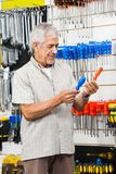 Customer Comparing Screwdrivers In Hardware Shop Royalty Free Stock Photos