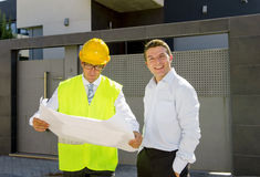 Customer and constructor foreman worker talking on new house building blueprints in real state business concept. Happy customer smiling and constructor foreman royalty free stock image