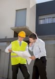 Customer and constructor foreman worker talking on new house building blueprints in real state business concept. Customer and constructor foreman worker with royalty free stock photo