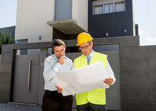 Customer and constructor foreman worker talking on new house building blueprints in real state business concept Royalty Free Stock Photography