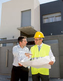 Customer and constructor foreman worker talking on new house building blueprints in real state business concept Stock Image