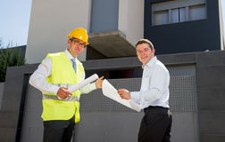 Customer and constructor foreman worker talking on new house building blueprints in real state business concept Royalty Free Stock Photo