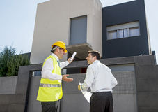 Customer and constructor foreman worker talking on new house building blueprints in real state business concept. Customer and constructor foreman worker with royalty free stock photography