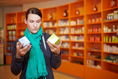 Customer doing price comparison. Customer doing a price comparison in a pharmacy stock photo
