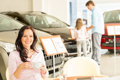 Customer drinking coffee in car dealership Stock Images
