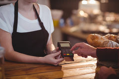Customer entering pin number into machine at counter Royalty Free Stock Images