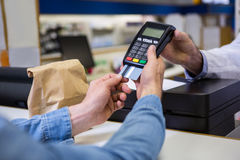 Customer entering pin in payment terminal machine Stock Photo