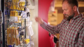 Customer examines accessories at the yacht centre. Middle-aged customer examining different accessories at the yacht centre. Bearded man dressed in checkered stock footage