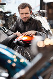 Customer examining motorcycle. Cheerful young men in leather clo Stock Photography