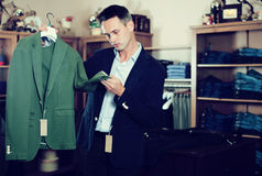 Customer examining suits. Adult customer examining suits in male cloths store Royalty Free Stock Photos