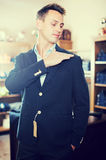 Customer examining suits. Cheerful young male customer examining suits in male cloths store Stock Photo