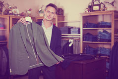 Customer examining suits. Happy young customer examining suits in male cloths store Royalty Free Stock Photography