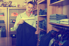 Customer examining suits. In male cloths store Stock Images