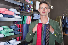 Customer examining ties in male cloths store. Young male customer examining ties at a male cloths store Stock Photography