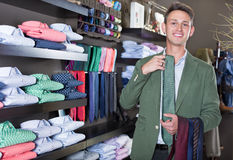 Customer examining ties in male cloths store. Young male customer examining a ties at a male cloths store Royalty Free Stock Images