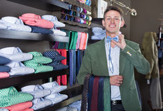 Customer examining ties in male cloths store. Young happy male customer examining ties in the male cloths store Stock Photo