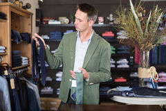 Customer examining ties in male cloths store. Young happy male customer examining a ties in the male cloths store Royalty Free Stock Photography