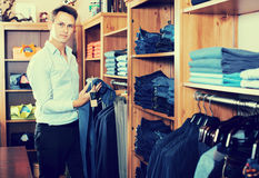 Customer examining trousers. Positive adult male customer examining trousers in male cloths store Stock Photo