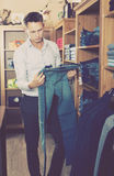 Customer examining trousers Royalty Free Stock Image