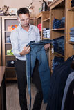 Customer examining trousers Royalty Free Stock Photography