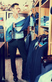 Customer examining trousers. Serious young male customer examining trousers in male cloths store Stock Photo