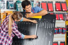 Customer Examining Wrench Using Board In Store. Young salesman with female customer examining wrench using board in hardware store Stock Photos
