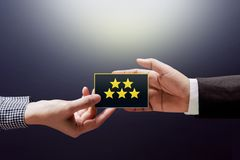 Customer Experience Concept, Happy Client Woman giving a Feedbac. K with Five Star Rating on Card into a Hand of Businessman Royalty Free Stock Photo