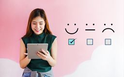 Customer experience concept, happy client woman holding digital. Tablet with a checked box on excellent smiley face rating for a satisfaction survey royalty free stock image
