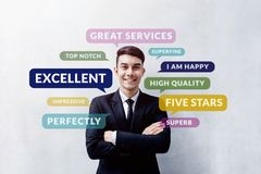 Customer Experience Concept. Happy Young Client standing at the. Wall, Smiling and Crossed Arms, Looking at camera. Surrounded by Positive Review in Speech royalty free stock photo