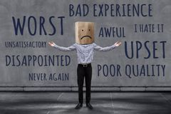 Customer Experience Concept, Unhappy Businessman Client with Sad. Ness Emotion Face on Paper Bag, Blurred Concrete Wall with Wording of Negative Reviews as royalty free stock photo