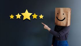 Customer Experience Concept. Woman Covered her head by Paper Bag with Happy Feeling Face and Pointing Hand to Five Star Services. Rating Satisfaction. Client`s stock photo
