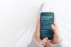 Customer Experience Concept. Woman lying on Bed to Reading Online Review via Smartphone before Buying Products and Services, More
