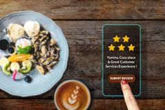 Customer Experience Concept. Woman using Smartphone in Cafe or R. Estaurant to Feedback Five Star Rating in Online Satisfaction Survey Application, Food Review royalty free stock photo
