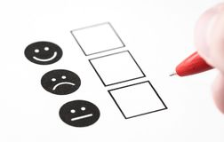 Customer experience survey, employee feedback questionnaire or business poll concept. Happy smile, neutral and sad frown faces on paper. Multiple choice stock photography