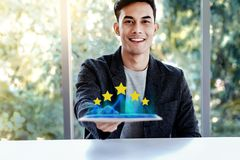 Customer Experiences Concept. Happy Young Man Sitting at the Desk and presenting his Five Star Rating in Online Survey. Via Digital Tablet. Smiling and Looking stock photos