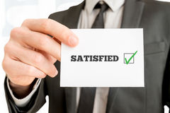 Customer feedback - Satisfied. Concept with a businessman holding up a card with a ticked check box from a survey or feedback report and the word Satisfied Stock Image