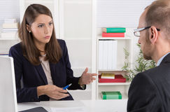 Customer and female financial agent in a discussion at desk. Royalty Free Stock Photos