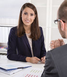 Customer and female financial agent in a discussion at desk. Royalty Free Stock Photo