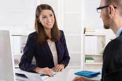Customer and female financial agent in a discussion at desk. Stock Images