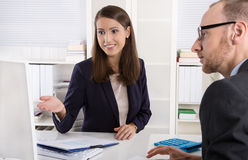 Customer and female financial agent in a discussion at desk. Royalty Free Stock Images