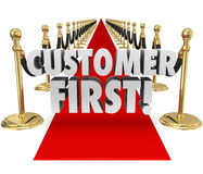 Customer First Words Red Carpet Top Priority Client Service. Customer First words on a red carpet to illustrate importance of placing priority on client service Stock Photo