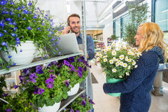 Customer With Flower Pot Looking At Florist Using Stock Images