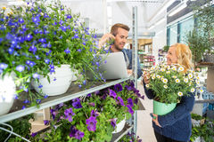 Customer With Flower Pot Looking At Florist Using Royalty Free Stock Photography